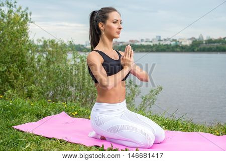 Fit woman in the prayer position meditating in nature