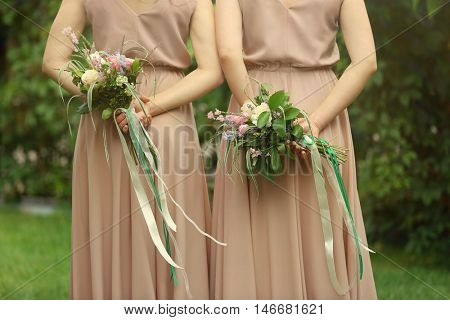 Beautiful bridesmaids holding bouquets
