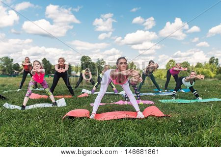 Portrait of smiling sporty women doing stretching exercises fitness class in parkland