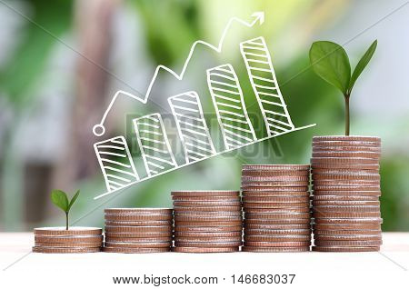 young plant grown to stack silver coin in business growth concept and have Business graph points to top.