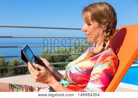 Middle aged dutch woman on orange sunlounger reading tablet on terrace