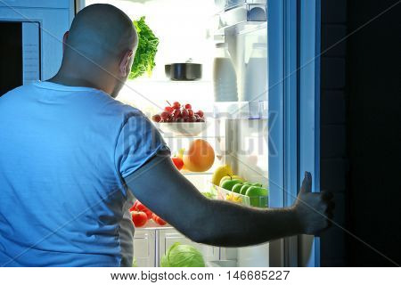 Man taking food from refrigerator