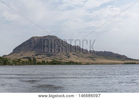 A butte with a lake on a cloudy day.