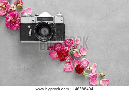 Vintage camera and colourful flowers on grey background