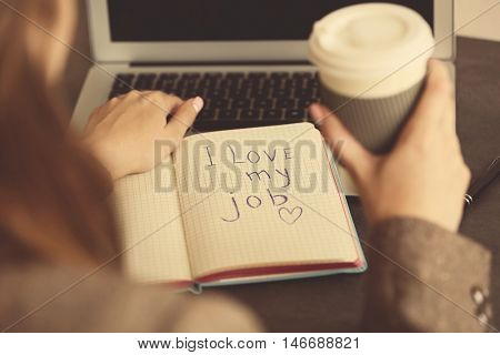 I love my job concept. Female hands with open notebook