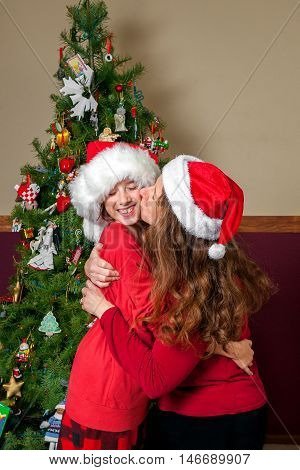 Christmas portrait of a mother kissing her daughter on the cheek by a fully decorated Christmas tree. Both are wearing Santa hats.