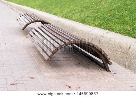 Two wooden benches in the form of an arc on the track in the park