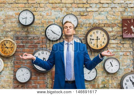 Be confident mean to be calm. Cropped shot of handsome businessman meditating front brick wall with different clock on it