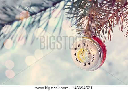 New Year and Christmas background - New Year Christmas ornament on snowy fir tree branch. New Year festive card with bokeh. Christmas and New Year background. Focus at the New Year clock. Shallow DOF.