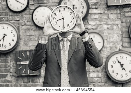 Time management. Black-white shot of young man in suit holding wall clock infront of his face against brick wall