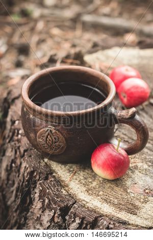 Clay Rural Cup With Hot Beverage And Red Apples On Wooden Stub.