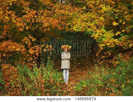 Young frowning girl with a wreath of autumn maple leaves on the head is on the forest path between trees