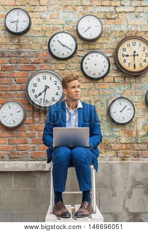 When ambition burns out. Shot of businessman looking anxious somewhere and holding his laptop, sitting near wall with clocks
