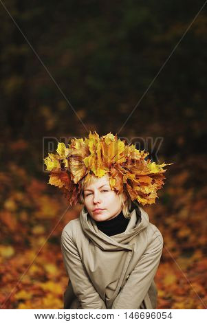 beautiful young girl in autumn park with wreath of leaves, close-up.