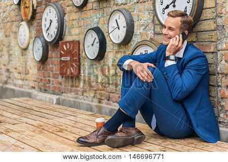 Businessman sitting on wooden floor and talking on smartphone with brick wall and cup of coffee on background