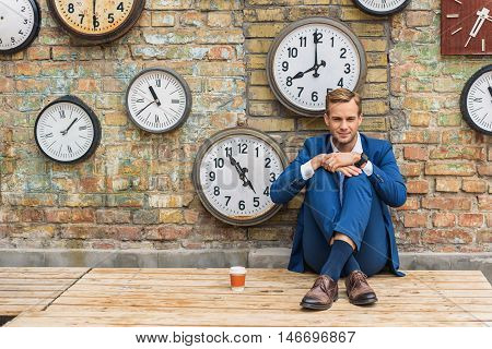 Considering challenging tasks. Shot of young businessman looking bored and tired, sitting behind brick wall with cup of hot drink
