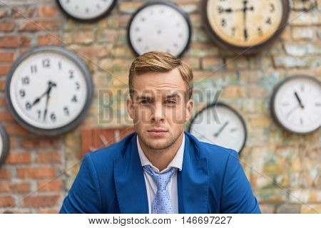 So many deadlines, so little time. Cropped shot of young businessman looking thoughtfully into camera and sitting on brick wall background