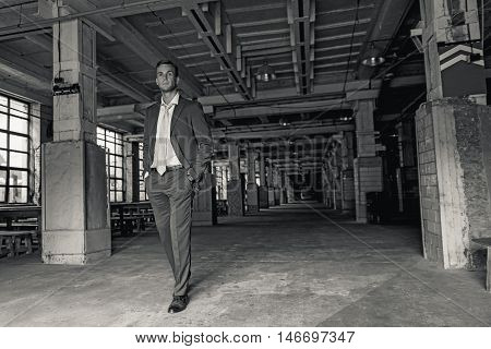 My business is my source of confidence. Black-white photo of man wearing suit and walking proudly in dark industrial hall