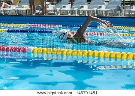 Backside view of the female swimmer who swims in the swimming pool outdoors. She wears a black-lime swimsuit, a white swim cap and swim glasses. Horizontal.