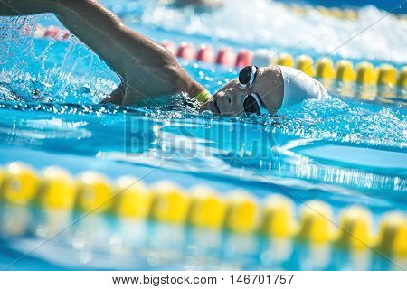 Attractive close-up photo of female swimmer in the motion in the swimming pool outdoors. She wears a black-lime swimsuit, a white swim cap and swim glasses. Horizontal.