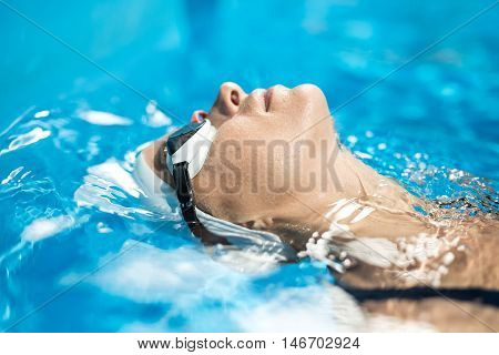 Horizontal close-up photo of female swimmer in the swimming pool. Girl swims on her back. She wears a white swim cap and swim glasses. Shoot from the side.