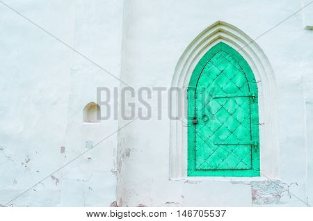 Architecture view of architecture details - old light green metal forged door with arcade on the white stone wall. Architecture background.
