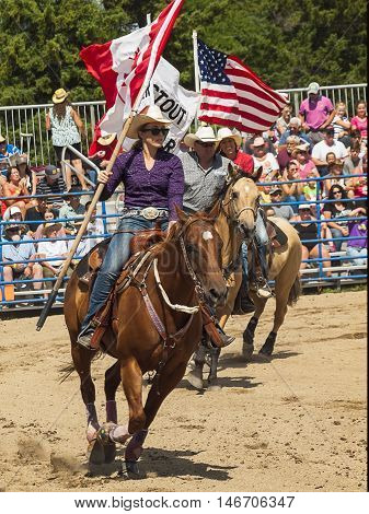 Rodeo. A man and a woman with the flags of Canada and America on horseback. Winnipeg. Canada.