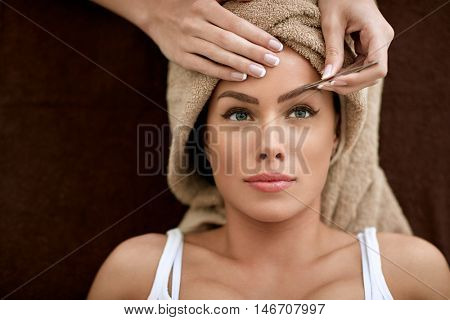 Beautiful woman receiving professional eyebrow shaping