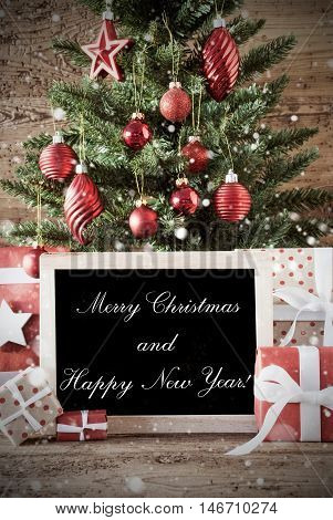 Nostalgic Christmas Card For Seasons Greetings. Christmas Tree With Balls. Gifts Or Presents In The Front Of Wooden Background. Chalkboard With English Text Merry Christmas And Happy New Yea