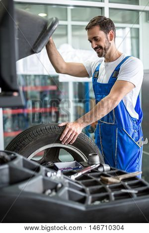 mechanic repairman installing automobile car wheel on tyre