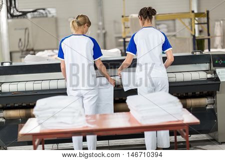 Women for ironing machine in dry cleaner