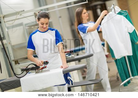 Satisfied worker ironing textile on ironing board