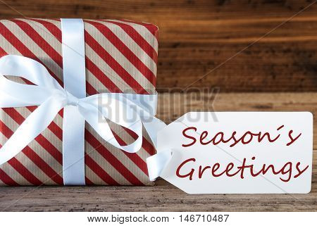 Macro Of Christmas Gift Or Present On Wooden Background. Card For Seasons Greetings, Best Wishes Or Congratulations. White Ribbon With Bow. English Text Seasons Greetings