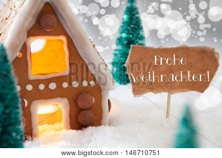 Gingerbread House In Snowy Scenery As Christmas Decoration. Trees And Candlelight For Romantic Atmosphere. Silver Background With Bokeh Effect. German Text Frohe Weihnachten Means Merry Christmas