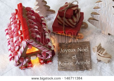 Label With French Text Joyeux Noel Et Bonne Annee Means Merry Christmas And Happy New Year. Gingerbread House On Snow With Christmas Decoration Like Trees And Moose. Sleigh With Christmas Gifts.