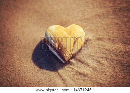 Stone heart on the beach in the waves, shallow focus