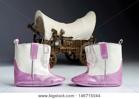 Cute Pink baby boots with covered wagon in background.