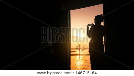 siluate image of woman capture sunset moment from hotel room