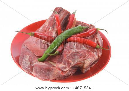 two fresh raw ribeye beef steak on red plate with red and green hot chili pepper isolated over white background rib eye