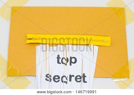 Top Secret destroying sheet of paper with yellow zipper as a shredder.