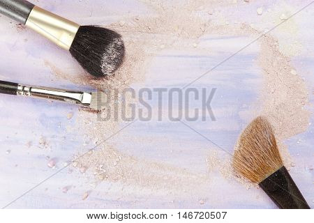 Makeup brushes on a light purple background with traces of powder and blush on it. A horizontal template for a makeup artist's business card or flyer design with plenty of copyspace