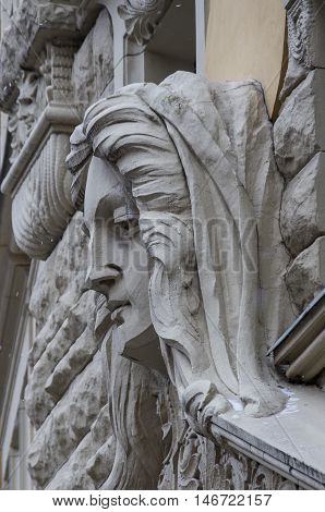 Woman's face sculpture. Art Nouveau house facade decoration in Riga old town Latvia