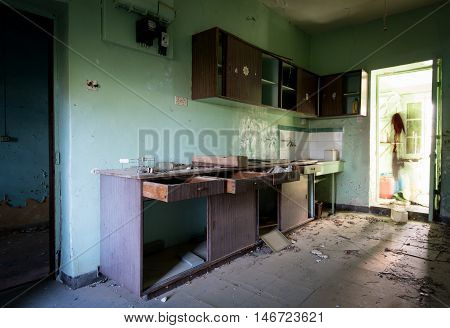 Interior of a dirty an empty demolished abandoned cuisine room with broken furniture open door an dirty floor