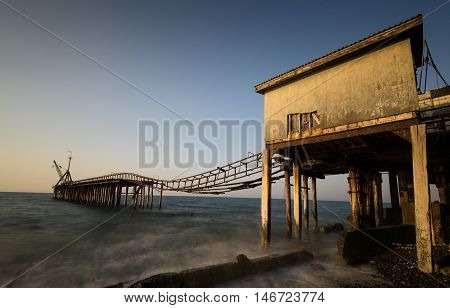 Seascape with old deserted industrial jetty during sunset at Karavostasi area near Leuka in Cyprus.