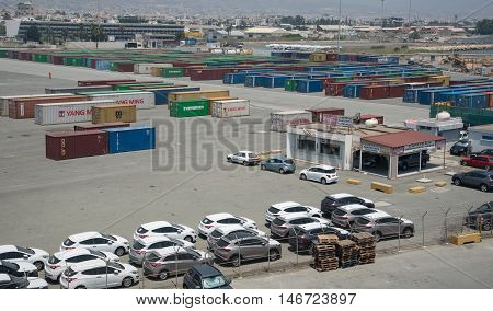 Limassol Cyprus - June 29 2016: New cars and cargo ship container boxes at the industrial harbor of Limassol in Cyprus