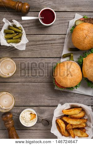 Different burgers and cheeseburger on wooden table with sauces fries pickles and lager beer top view with copy space