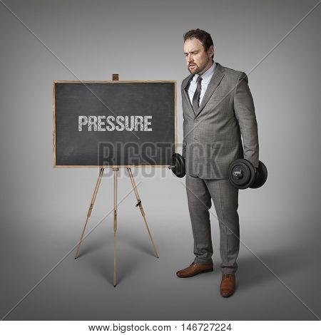 Pressure text on blackboard with businesssman holding weights