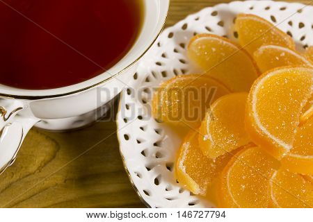 Gummi candies and cup of tea on a wooden background