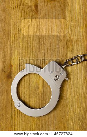 Tool restriction of freedom - the handcuffs. Handcuffs on a wooden surface.