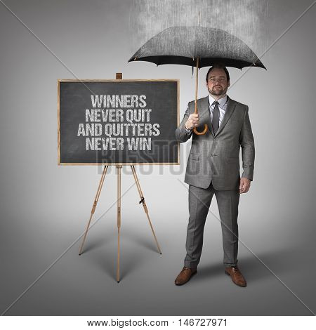 Winners never quit and quitters never win text on blackboard with businessman and umbrella